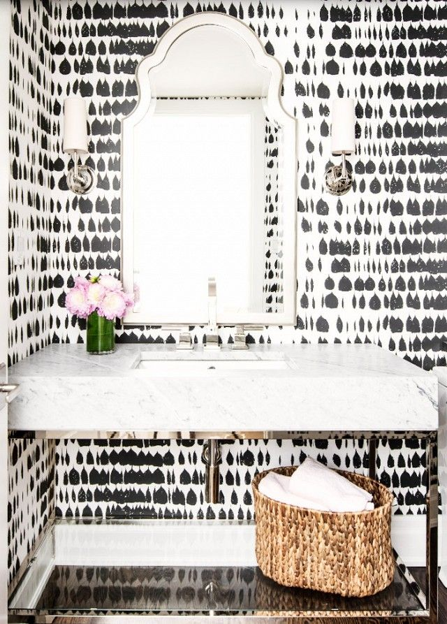 The crisp edges and hard surfaces of the vanity in this powder room are a great match for the graceful lines of the curved mirror. Though the wallpaper's pattern is graceful and painterly,...