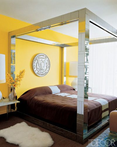 CHROME BED    A giant silver-dollar replica from a thrift shop is set against walls painted Benjamin Moore's Bold Yellow in the master bedroom of Jonathan Adler and Simon Doonan's Florida condo; the Paul Evans chrome bed is dressed in a handwoven wool coverlet by Adler.