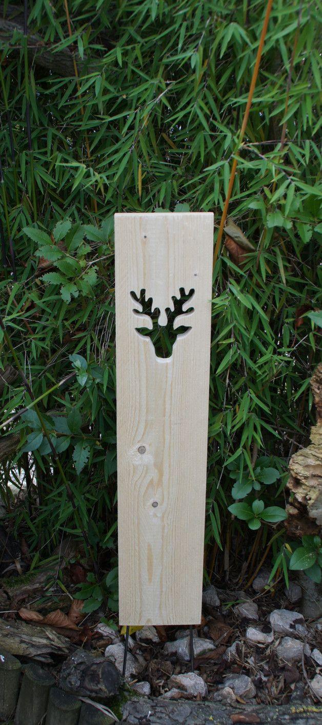 Die **Holzstele** mit **Elchkopf** ist aus unbehandeltem Nadelholz mit sägerauher Oberfläche und 2 Eisenstangen zum Einstecken in den Boden. Unregelmäßigkeiten im Holz (z.B. Holzwurmlöcher,...