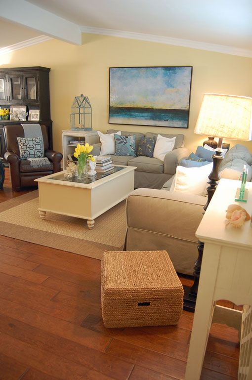 Explore this lovely, seaside-inspired home makeover that will leave you feeling ready to plan your next home update. The wicker accents, neutral color wall paint, and beachy paintings tie this room together. Try BEHR paint in Sunkissed Yellow in your living room to get this look.