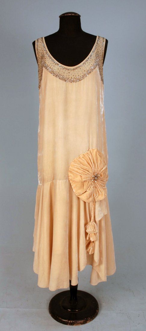 1920s evening dress - the dress of this time had a straight silhouette with no indentation at the waistline.  Evening dresses were shorter and usually sleeveless with either a rounded or v-neckline.  Ornamenting an evening dress was popular as well.  Many times the skirt was either floating, draped, or layered.
