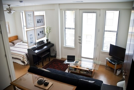 studio apartment- love the floating photos used as a divider