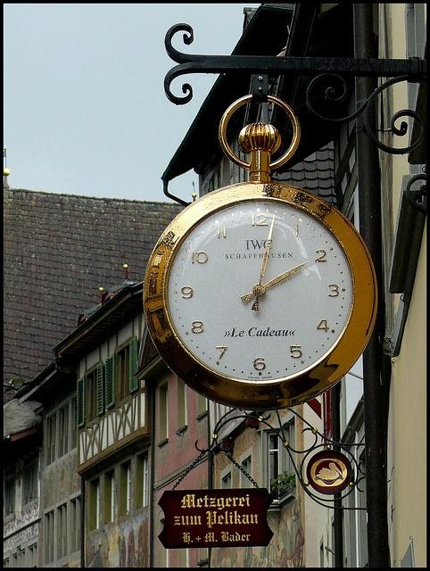 Llamativo rotulo con forma de reloj, grande y dorado, indicando buena calidad suiza.  Alejandro Estevez