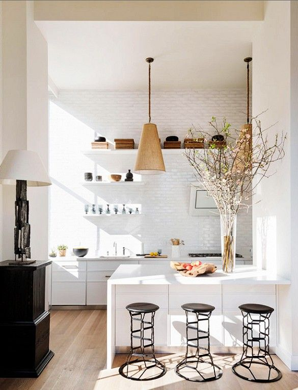 White tiled kitchen with sculptural stools, high ceilings, and beautiful natural light.