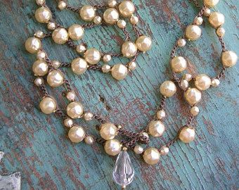 An ultra-long beaded necklace dotted with clusters of faux pearls and silvery faceted semi-precious stones. Wear it long or double it, then layer on your favorite chains or 3 Divas Studio necklaces!  Silver glass pearls and sparkling hematite on a delicate yet sturdy crocheted chain that closes with a petite abalone button and loop.  Approximately 34 inches. Show layered with another 3 Divas Studio necklace available separately.  Shop for limited production and one-of-a-kind necklaces by 3…