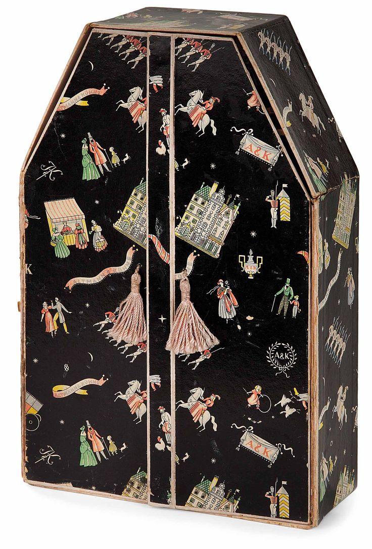 """Dagobert pêche (1887-1923) coffret à bijoux et à rubans, formant petite armoire rectangulaire à fronton à pans coupés, en carton lithographié à décor polychrome sur fond noir de personnages costumés, monuments et ornements. il ouvre par deux vantaux, munis de miroirs internes, sur un intérieur aménagé de cinq tiroirs, prises en passementerie. mentions """"a.k."""" et """"altmann & kühne"""". (fragilité aux attaches des portes). haut. 25,1 cm - larg. 16,7 cm - prof. 6,5 cm"""