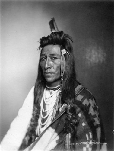 Weasaw, a Shoshone Native American man wearing a beaded necklace, blanket, feather, and fur-wrapped hair. This photograph was shot by the Rose & Hopkins studio during Denver's Festival of Mountain and Plain circa 1896-1899 - History Colorado Collection