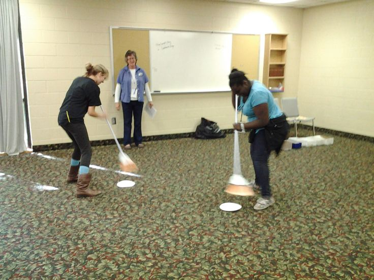 Clean Sweep students use brooms to sweep paper plates with parts of the verse across the room. they then assemble it and quote it.