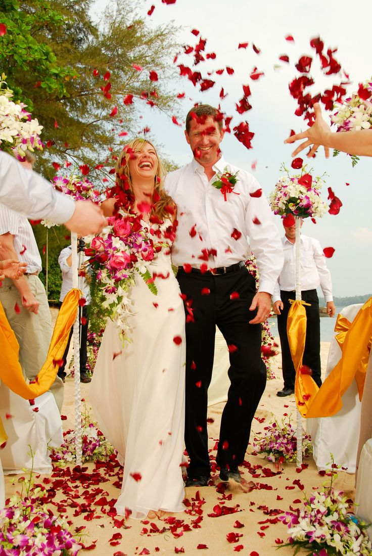 Happy couple enjoying a flower shower after their beach wedding ceremony. http://www.wedding-phuket.com