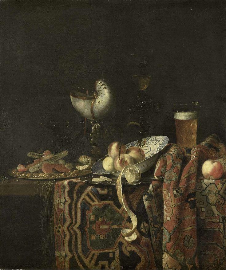 Georg Hainz | Still Life, Georg Hainz, 1666 - 1700 | Stilleven op een tafel met een Perzisch kleed. Op een vergulde zilveren schotele liggen suikergoed en koekjes, rechts een Chinese schotel met perziken. Vooraan een geschilde citroen. Achter verschillende glazen, rechts een glas met bier, in het midden een nautilusbeker.