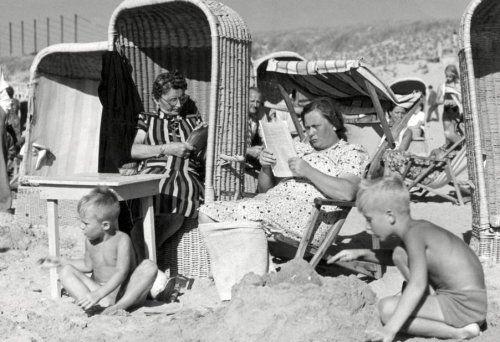 Zandvoort (Nederland) Op het strand zitten moeders geheel gekleed in   strandstoelen gezeten, te lezen. Twee jongetjes spelen aan hun voeten in   badkleding.