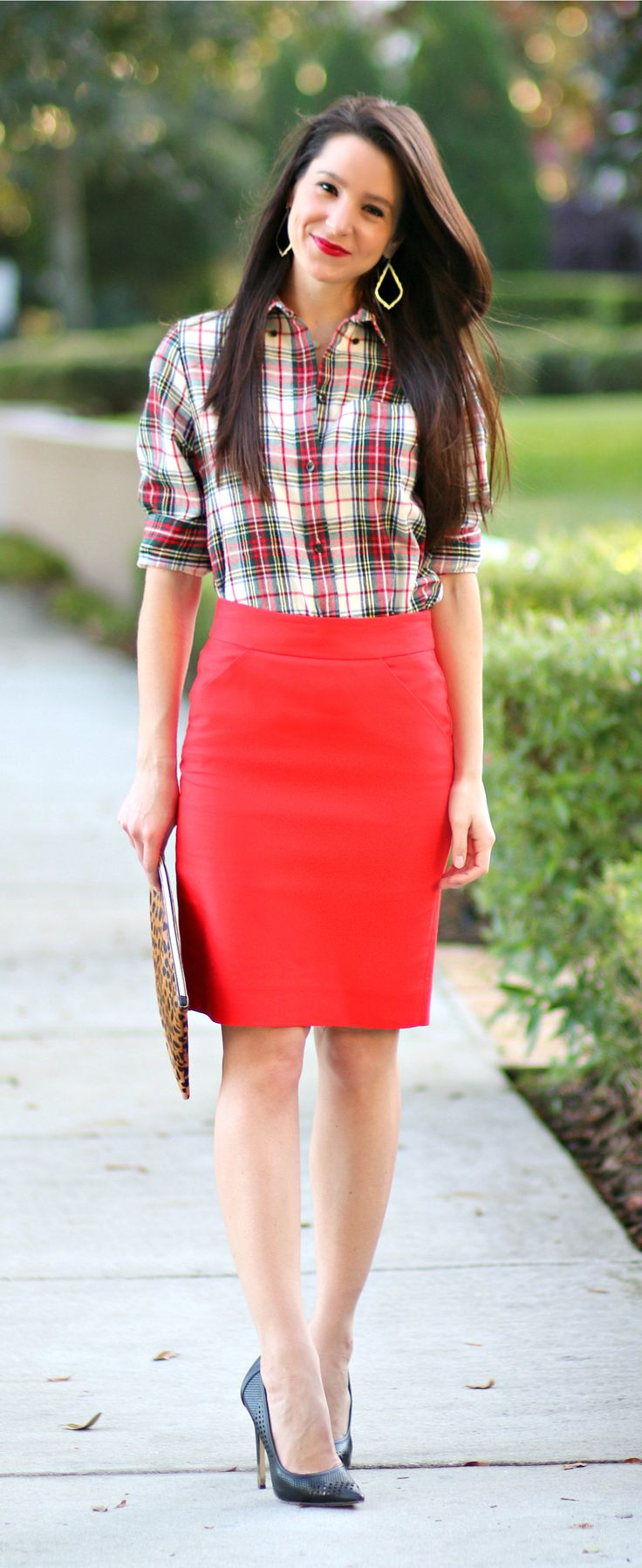How to wear a red pencil skirt to work in December! Love this festive holiday look. J.Crew Factory red pencil skirt with a Scotch plaid flannel shirt, leopard clutch, and black perforated pumps.