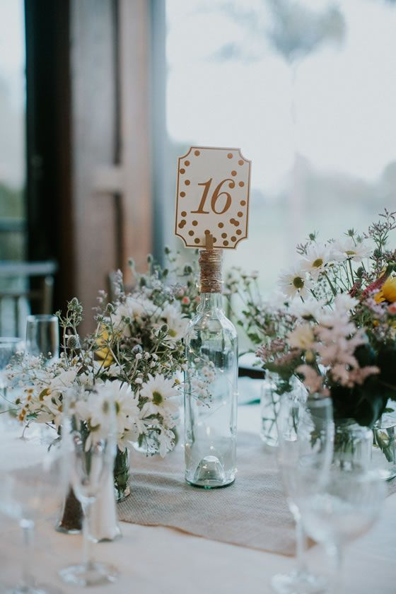Table numbers with gold dots, held up by a glass bottle. Springtime wildflowers make such a fresh tablescape //    Seafoam & Coral Ventura Beach Wedding | Wedgewood Ventura