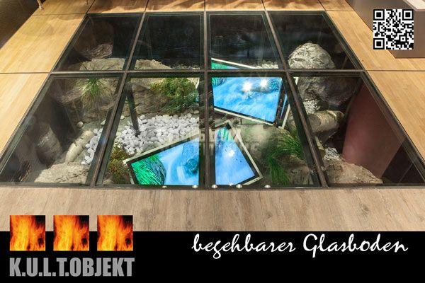 Unter den begehbaren Glasboden wurde eine Outdoor-Szene mit Felsen, Baumstämmen und Pflanzen nachgestellt, Über die integrierten Bildschirme ist ein quellender Gebirgsbach zu sehen,