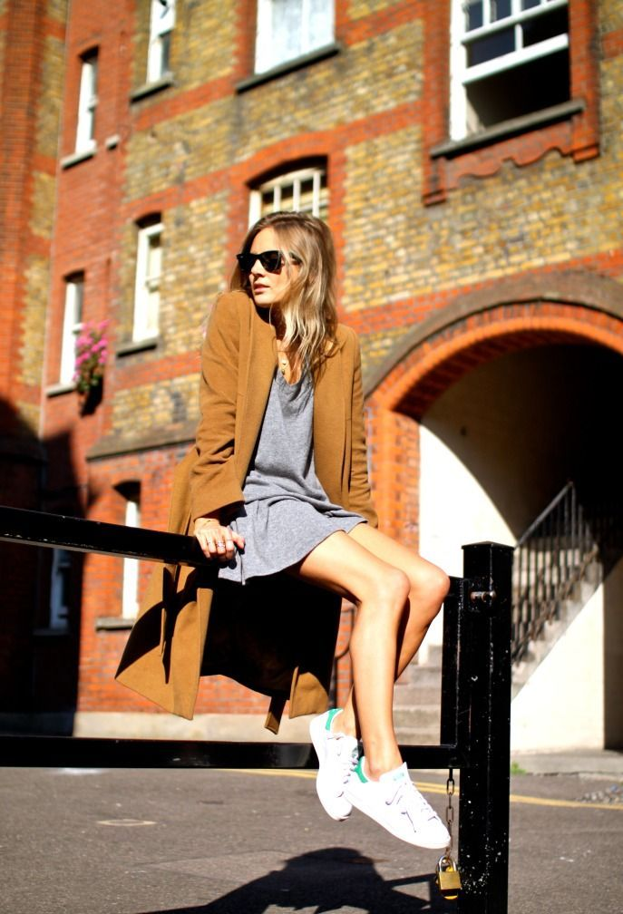 Lucy Williams is wearing a grey sweater and skirt from Ganni, Stan Smith trainers from Adidas, vintage coat from Vestiaire Collective