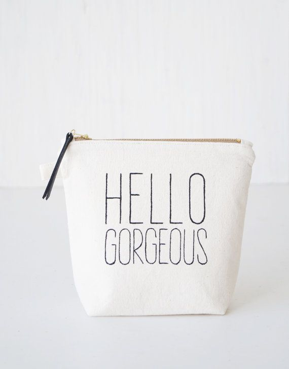 Add a little spice to your daily life with this cute, friendly and very practical makeup pouch. Carry around your makeup and other beauty tools safe in this boho chic meets classy rustic makeup bag in neutral off-white color with a handpainted text HELLO GORGEOUS. The pouch combines natural, old-school materials with modern styling. SIZE Approx. 17 cm / 6.7 wide (on the top) x 15 cm / 6 height 11 cm / 4.3 wide (on the bottom) x 6 cm / 2.4 depth (on the bottom)  MATERIALS Exterior & lining…