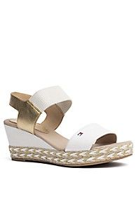 Tommy Hilfiger women's shoe. Two classics combine to create one standout sandal. Walk tall (and comfortably) the platform delivers a boost while the webbed straps keep your feet firmly in place. • Slide silhouette in leather and cotton. • 3.5'' platform, rubber sole. • Spot clean.• Imported.
