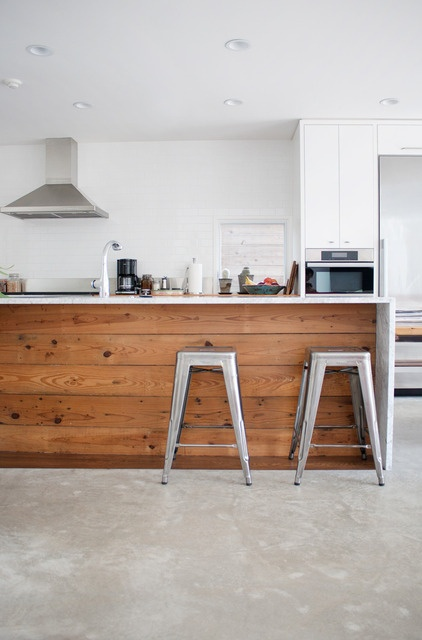 Use of benchtop running down to connect with floor. Use of wood on side panelling