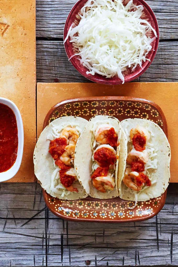 These garlic shrimp tacos are a mashup of flavors which work really well together. Buttery, garlicky shrimp served on a bed of tangy vinegar slaw topped with a sharp arból chile salsa with a touch of Mexican oregano.