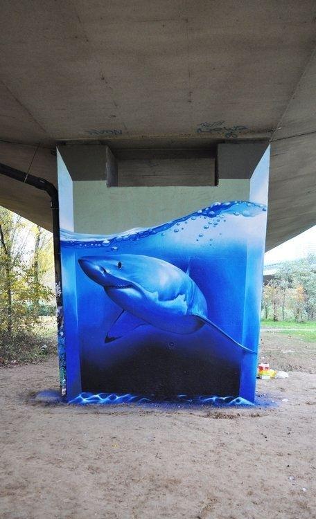 een graffiti kunstwerk. Het is een redelijk realistische haai die gespoten is op een zuil van een brug. de zuil is de drager