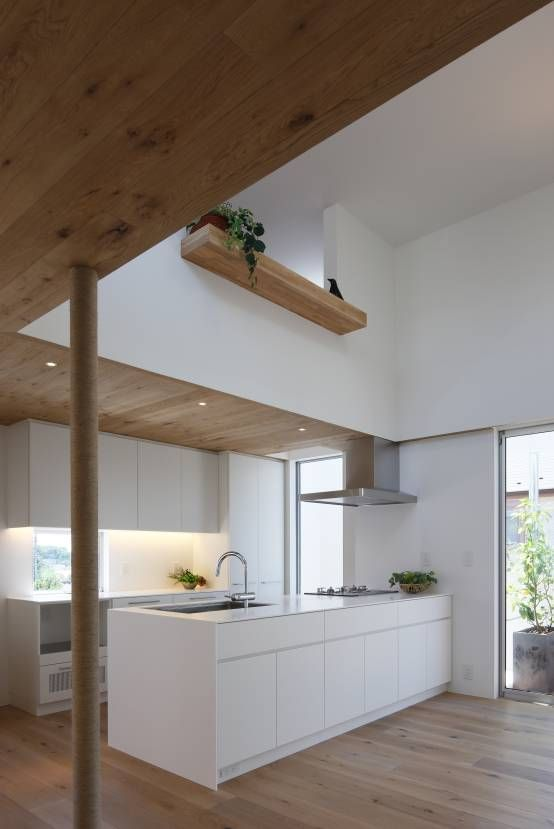 Modern, white kitchen with stainless steel appliances and wooden floors, wooden roof and high ceilings. By: アトリエ スピノザ