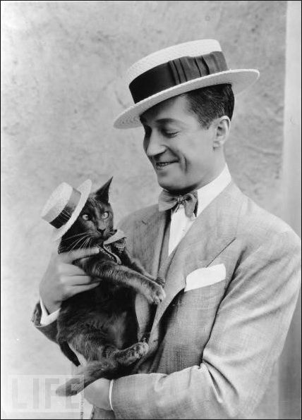 "Maurice Chevalier and feline actor ""Puzzums,"" photographed by Orville Logan Snider ca. 1925."