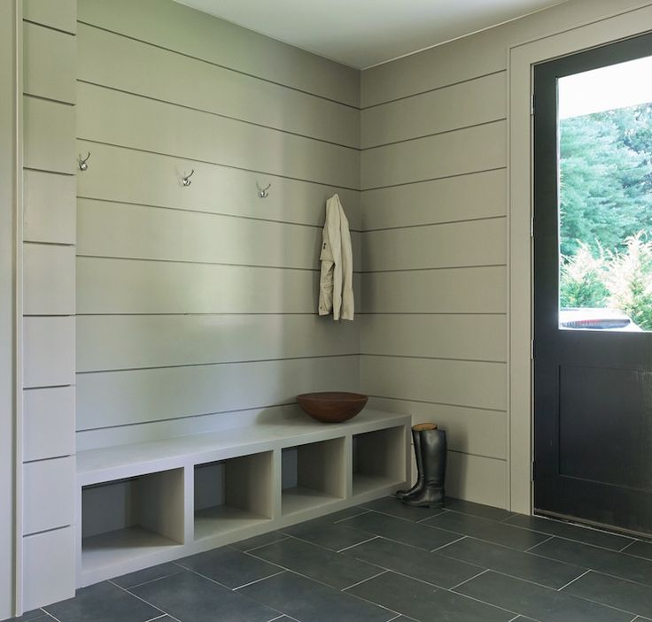 Modern gray mudroom features tongue and groove walls painted gray accented with hooks over a gray built-in bench with open cubbies atop a slate staggered tile floor next to a black back door.