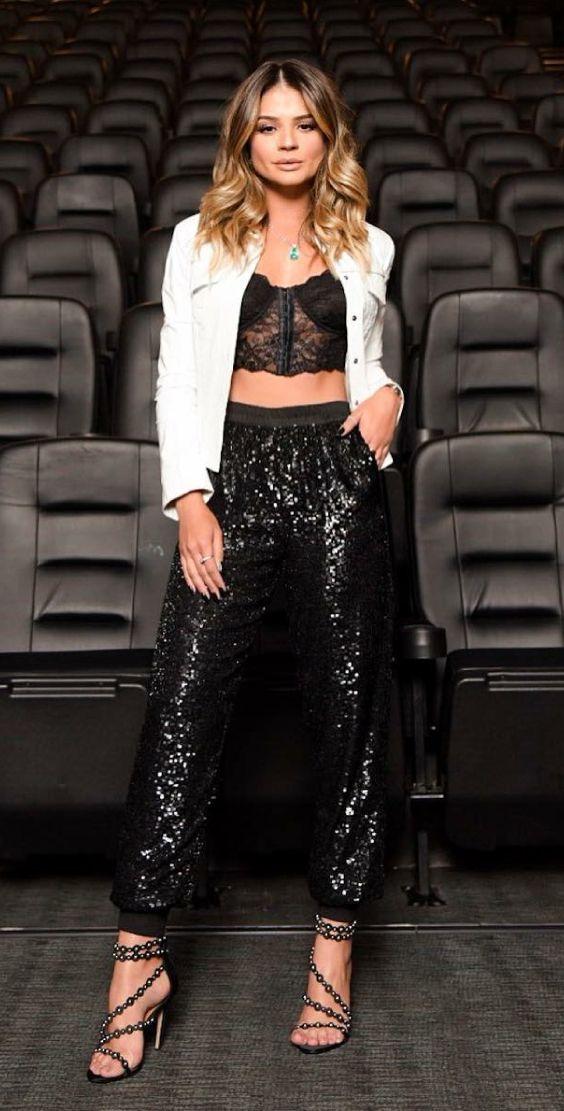 f56416613 Jaqueta branca, top cropped de renda, estilo lingerie, calça jogging preta  de paetês, sandália de tiras preta