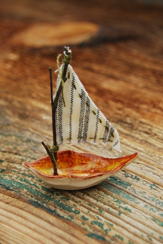 Often I dream of sailing away…  This little ship may just take me there…    Made of kiln fired clay and a tiny twig mast  With mattress ticking sails blowing in the breeze    I could TOTALLY make this!