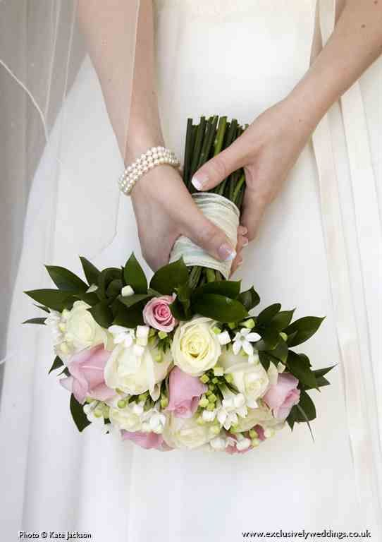 Bridal hand-tie bouquet of pink roses, pale blush pink Sweet Avalanche roses and white bouvardia, by Exclusively Weddings. Photo by Kate Jackson
