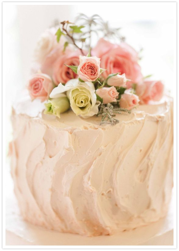 small, simple cake with fresh flowers and buttercream icing just for cutting