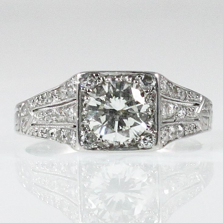 Antique & Unique Engagement Ring -   Round center diamond (.68 carats, I, VVS2) in squared platinum mounting with smaller round diamonds