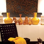 Black & mustard yellow foyer design with black walls paint color, burnt orange coral wall art, glossy white lacquer credenza, mustard yellow glossy vases, mustard yellow throw and Knoll's black Risom Lounge Chair.