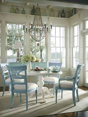 Gorgeous painted coastal blue chairs, white washed round table, texture rug, lovely jug of flowers, undressed windows and high shelf with vintage finds & old bottles and glass love! x
