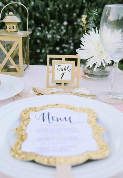 classic gold place card holder frames show guests to their seats and serve as special wedding favors too in keeping with the gold palette lanterns and