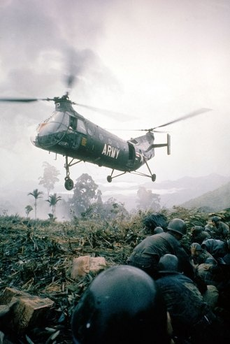 """""""U.S. H-21 helicopter arrives in combat area with supplies for a Vietnamese patrol. It flew out wounded soldiers."""""""