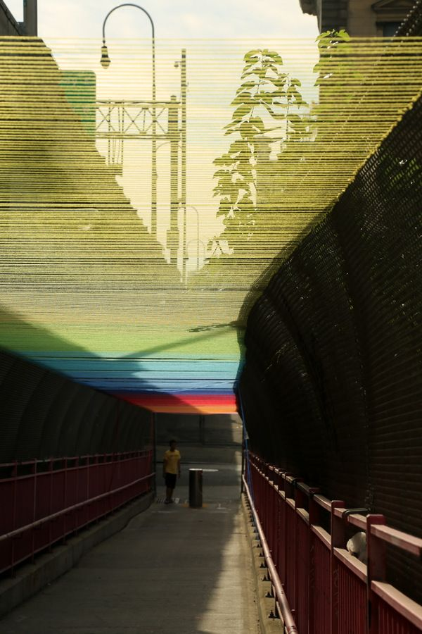 Minneapolis-based street artist Hottea's installation titled Rituals. Rainbow-hued yarn strung above the pedestrian walkway of the Wiliiamsburg Bridge.