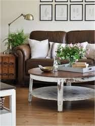 A great table with slightly distressed look add brown couch and cushions with brown and white accents - the prints on the wall adds to room