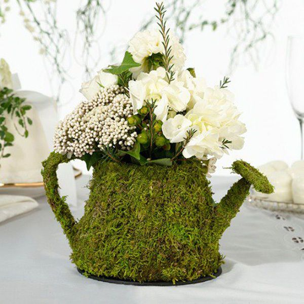 Mossy floral watering can centerpiece: Use these moss table decorations as the focal point to your guest tables to achieve overall Alice in Wonderland theme. This whimsical watering can also comes in teacup form, making it the perfect vase for small florals at a garden wedding.
