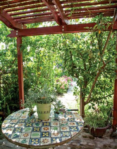 Although this pergola sits high above the tile-topped table, the close spacing of the boards overhead helps cast a deep shade over the whole.