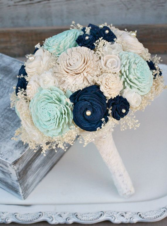 This is a brides bouquet This sweet bouquet mixes hand dyed pastel mint green sola flowers with assorted navy blue, neutral ivory cream sola wood