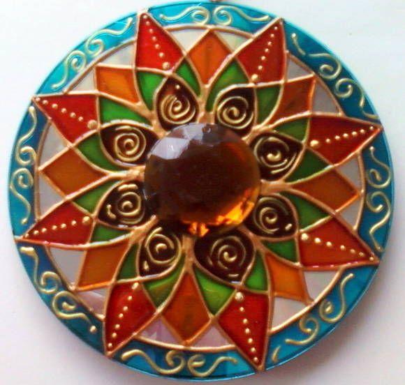 Mandala feita em CD reciclado, tamanho 12cm de diâmetro. Pintura vitral, decorada com pedra acrílica e tinta relevo dourada. Com gancho de metal para ser pendurada na parede. R$ 18,00
