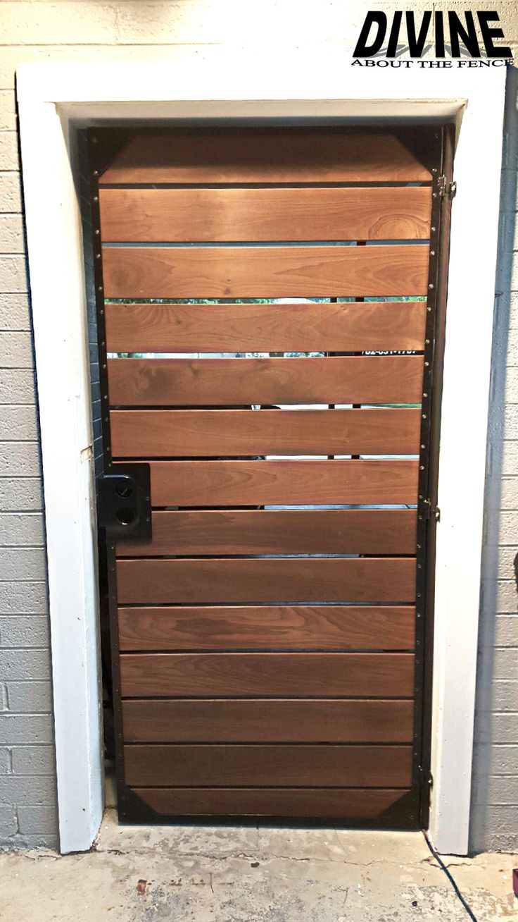 Modern slat wood security door installed and designed by divine about the fence