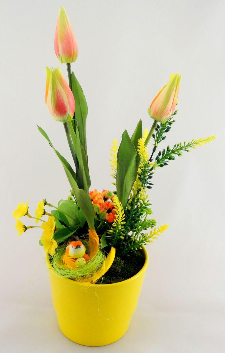 www.abgHomeArt.pl Ręcznie wykonany z dbałością o każdy szczegół wielkanocny stroik w żółtej ceramicznej osłonce z kwitnącymi tulipanami i kwiatuszkami w żółto-pomarańczowej kolorystyce otulone mchem chrobotkiem. Udekorowany ptaszkiem w gniazdku i jajeczkami.    Efektowna i radosna wielkanocna dekoracja, która pięknie przyozdobi stół, komodę, czy też kominek, a także wprowadzi powiew wiosny. Idealny do każdego wnętrza.