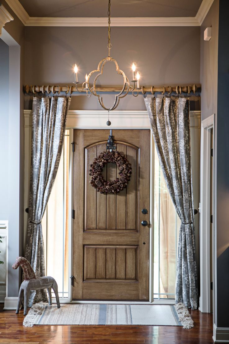 Curtains over the front door foyer add privacy and style.  Chandelier by Gabby, rod from Restoration Hardware and curtains Pottery Barn #gabbydecor #shapingyourspace.com #foyerwithcurtains