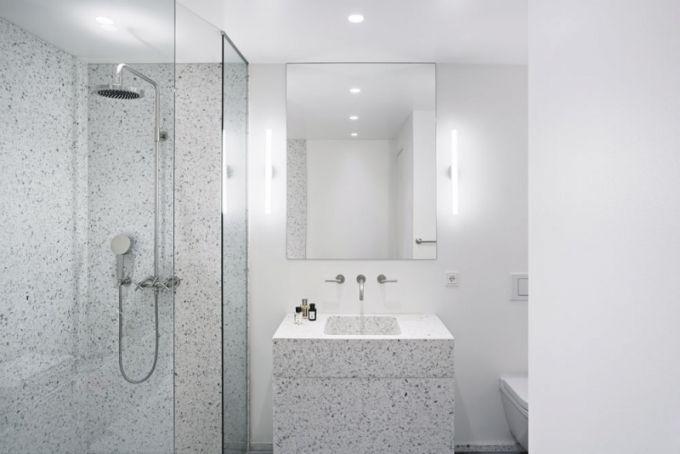 Masivní umyvadlo a obložení sprchového koutu z teraca vnáší do jinak bílé koupelny jemný mozaikový efekt