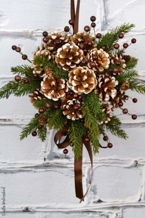 Pine Cone DIY Kissing Ball: You can't go wrong with a DIY Christmas kissing ball! Make this one with a styrofoam ball and faux greenery for a lasting Christmas decoration. Find more easy, rustic, and cool DIY Christmas craft ideas that can decorate your home this Christmas here.