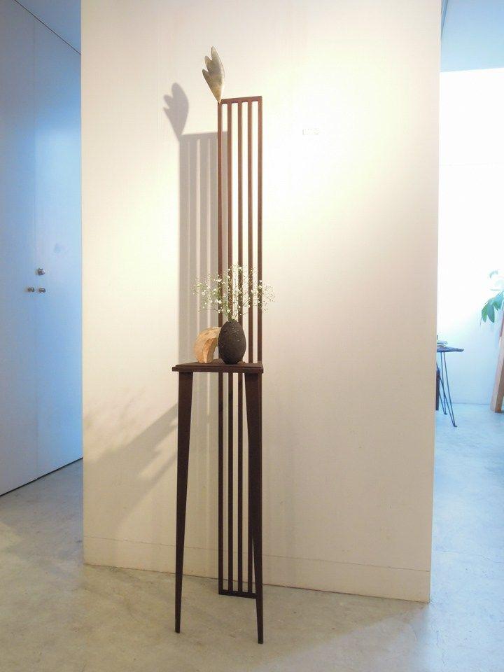 鉄で出来ている実際に座れる椅子のオブジェ。全体的に細身で、すっきりした格子状のハイバックに切り欠いた座面と、スタイリッシュなデザインでまとまっています。 花瓶を飾った設置例写真です。
