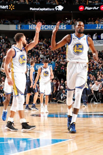287336d5e8fc Stephen Curry and Kevin Durant of the Golden State Warriors exchange high  fives during the game against the Dallas Mavericks on January 3 2018 at the.