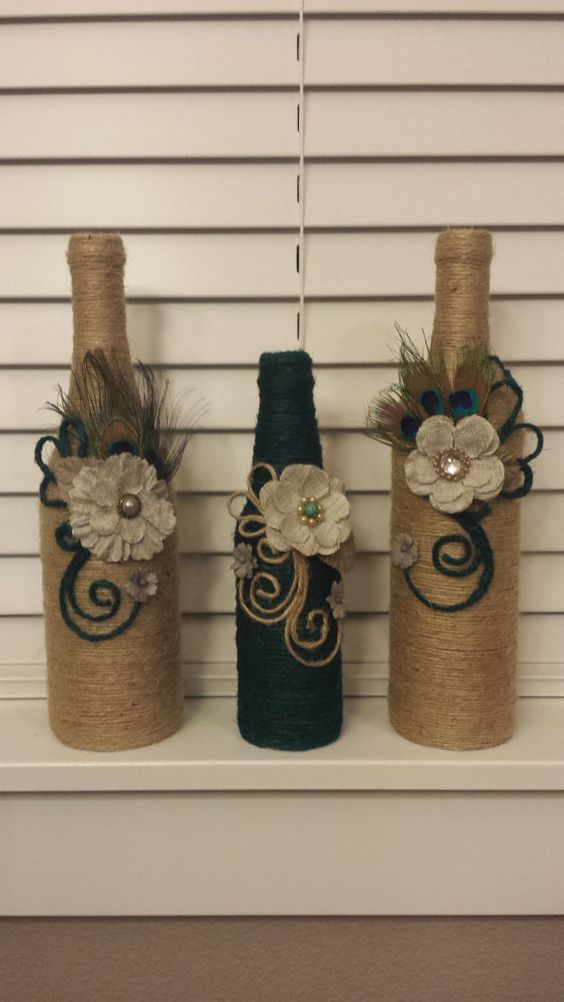 Set of 3 jute twine wrapped wine bottles. Beautiful modern decoration touch on them. Fabric flowers. Peacock feathers. Perfect for home: